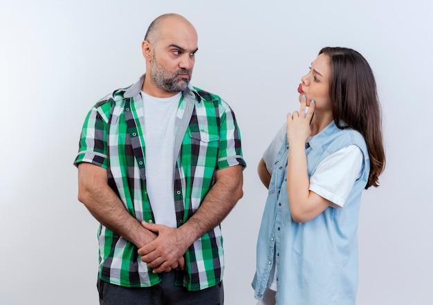 Casal adulto carrancudo, homem de mãos dadas, e mulher pensativa tocando o queixo, ambos olhando um para o outro, isolado na parede branca