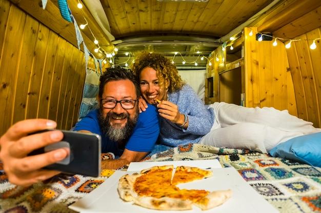 Casal adulto comendo pizza e tirando uma selfie dentro de uma velha clássica van de madeira feita em casa vintage em viagens de férias juntos, sorrindo e se divertindo