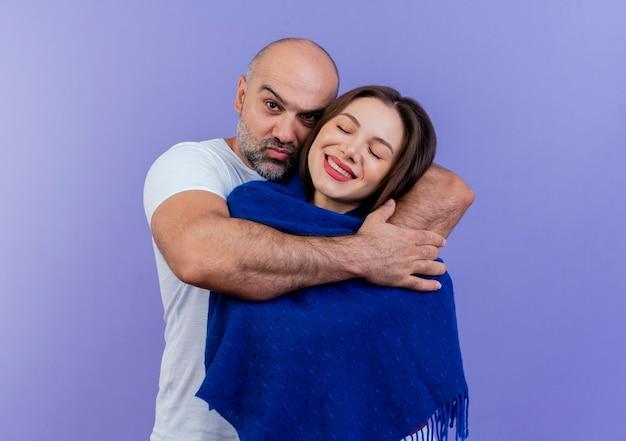 Casal adulto confiante homem olhando e segurando uma mulher feliz envolta em um xale com os olhos fechados Foto gratuita
