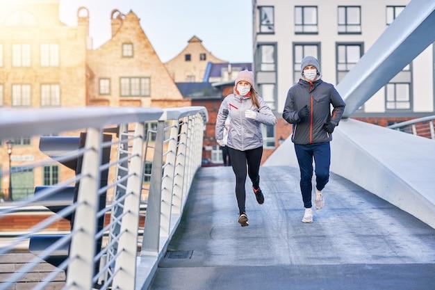 Casal adulto correndo na cidade mascarado durante a pandemia de bloqueio