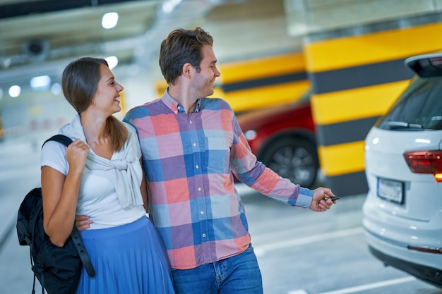 Casal adulto deixando o carro no estacionamento subterrâneo