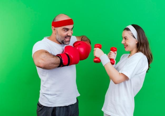 Casal adulto desportivo usando bandana e pulseiras impressionou o homem usando luvas de boxe, mantendo as mãos juntas, mulher sorridente segurando halteres olhando