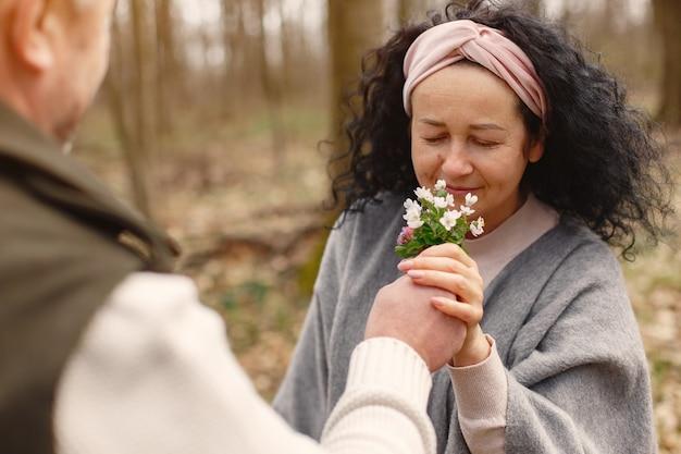 Casal adulto elegante em uma floresta de primavera
