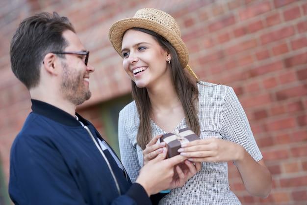 Casal adulto em um encontro na cidade, homem dando um presente