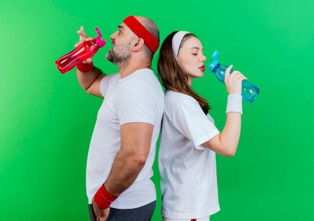 Casal adulto esportivo usando bandana e pulseiras em pé, costas com costas, bebendo água de uma garrafa