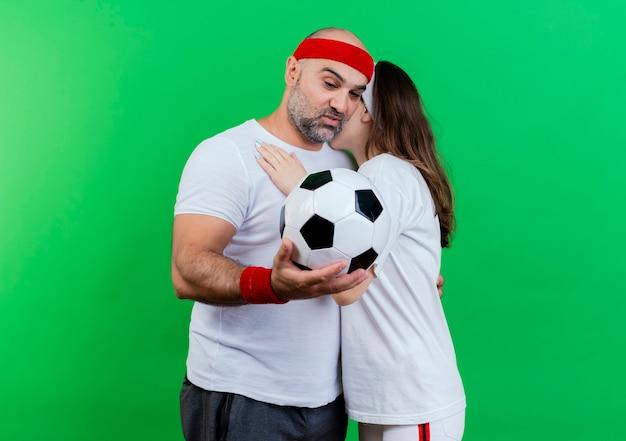 Casal adulto esportivo usando bandana e pulseiras se abraçando, impressionado homem segurando e olhando para uma bola de futebol