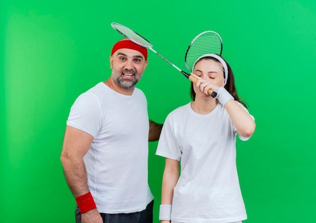 Casal adulto esportivo usando bandana e pulseiras segurando raquetes de badminton impressionou o homem olhando e a mulher tocando sua cabeça com a raquete com os olhos fechados