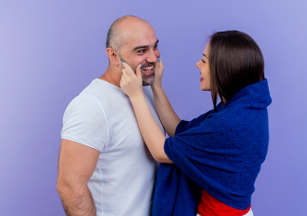 Casal adulto feliz enrolado em um xale beliscando as bochechas de um homem sorrindo e olhando um para o outro Foto gratuita