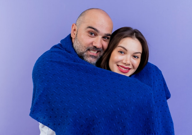 Casal adulto feliz enrolado em um xale sorrindo e olhando