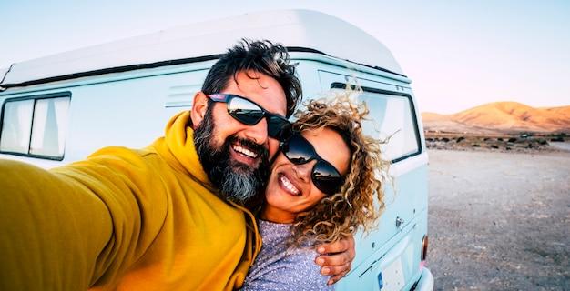 Casal adulto feliz sorri e se diverte tirando uma foto de selfie com uma velha van clássica vintage