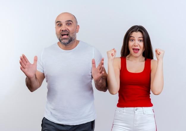 Casal adulto impressionado homem estendendo as mãos mulher cerrando os punhos ambos olhando