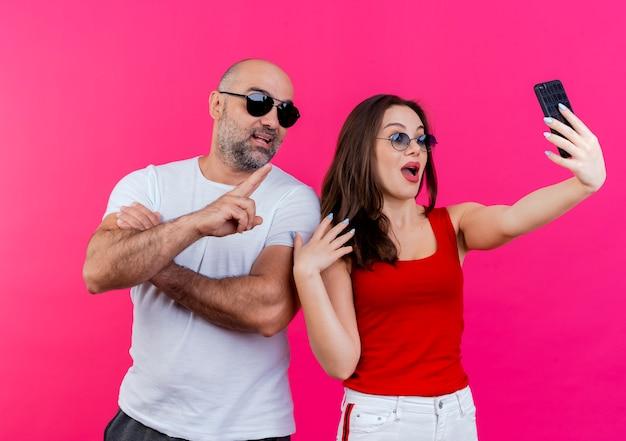 Casal adulto impressionado usando óculos escuros, homem fazendo sinal de paz, mulher mantendo as mãos no ar tirando selfie
