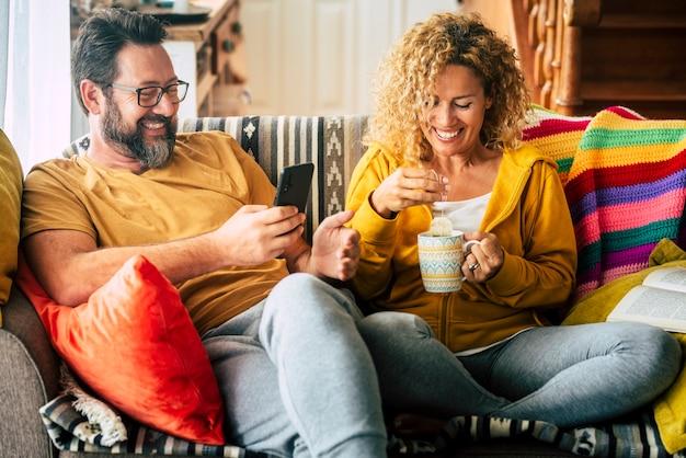 Casal adulto jovem alegre em casa toma café da manhã juntos, bebendo chá e olhando para o telefone - pessoas modernas em casa atividade de lazer interna - vida de amor e relacionamento