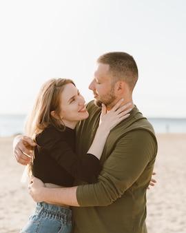 Casal adulto jovem em pé na praia, olhando um para o outro.