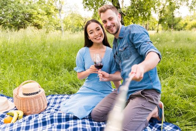 Casal adulto multirracial sentado tomando selfie com vara