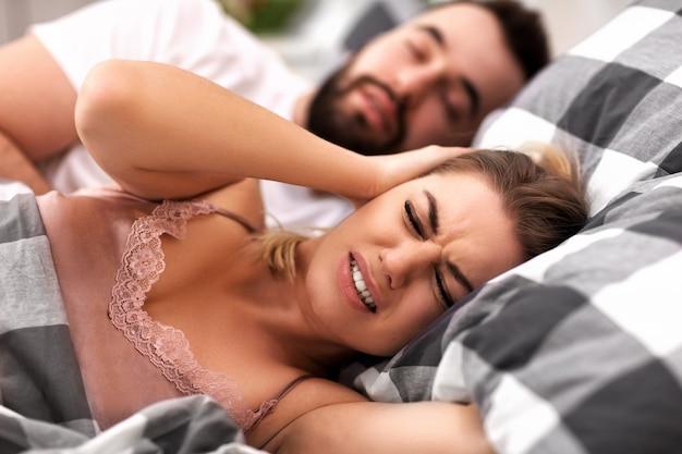 Casal adulto na cama com problema de ronco