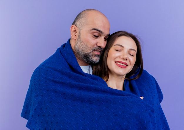 Casal adulto satisfeito enrolado em um homem xale olhando para baixo, mulher sorrindo com os olhos fechados