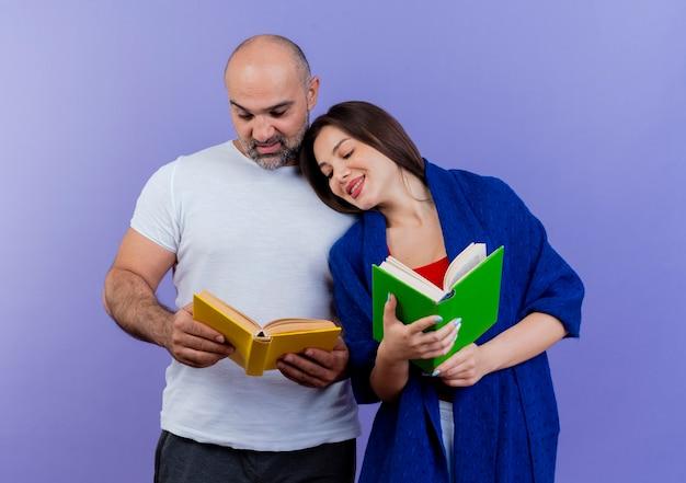 Casal adulto satisfeito, mulher envolta em xale, segurando o livro e olhando para o livro masculino