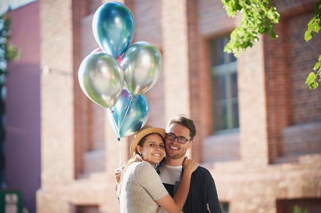 Casal adulto se abraçando em uma caminhada pela cidade, segurando balões