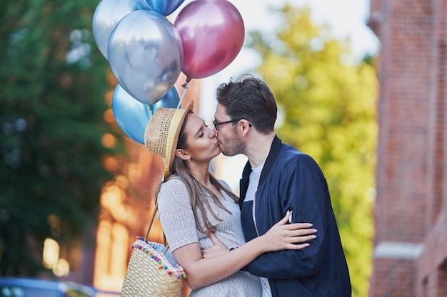 Casal adulto se beijando em uma caminhada pela cidade, segurando balões