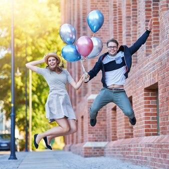 Casal adulto segurando balões e pulando enquanto caminha pela cidade