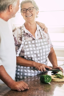 Casal adulto sênior alegre em casa trabalhando juntos na cozinha cortando vegetais frescos da estação prontos para cozinhar para um almoço saudável