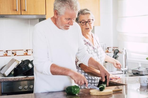 Casal adulto sênior caucasiano em casa preparando o jantar ou o almoço juntos