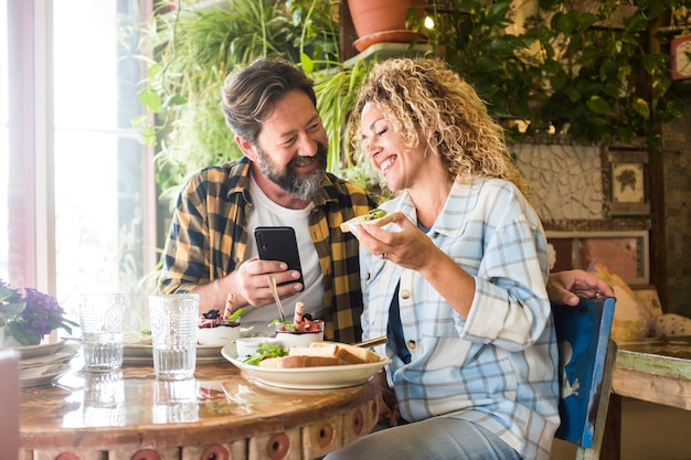 Casal adulto sorri e aproveita o almoço e a videochamada, sentado no bar e rindo junto com a felicidade - as pessoas, homem e mulher, usam o celular e fazem um brunch no restaurante