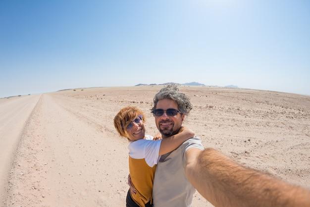 Casal adulto tomando selfie na estrada de cascalho no deserto do namibe, namib naukluft national park, principal destino de viagem na namíbia, áfrica
