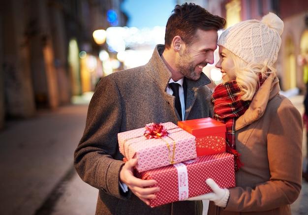 Casal afetuoso com pilha de presentes