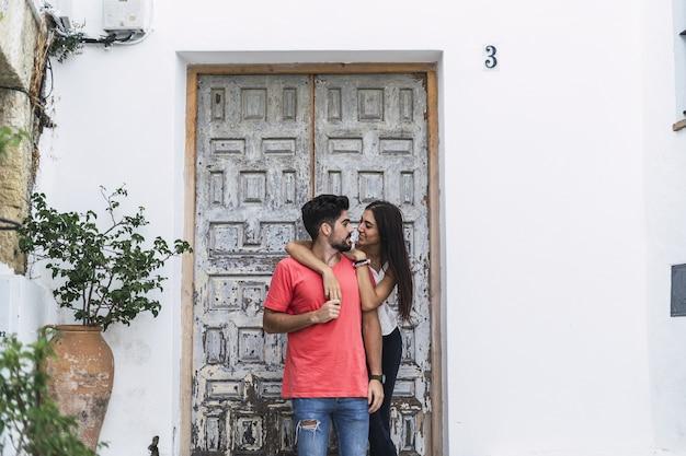 Casal afetuoso junto a uma parede decorada