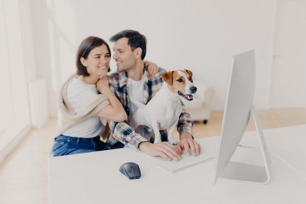 Casal afetuoso no amor abraça e vai se beijar, assistir filme romântico no computador moderno, cão de raça, focado no monitor com interesse