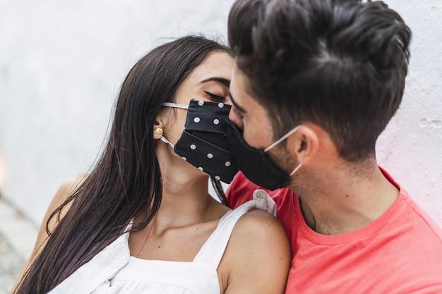 Casal afetuoso usando máscaras e se beijando