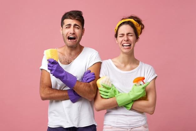 Casal aflito em camisetas brancas e luvas segurando esponjas e spray de limpeza sendo chateado por não querer fazer a limpeza durante os fins de semana. masculino e feminino com expressão chateada enquanto vão limpar a casa