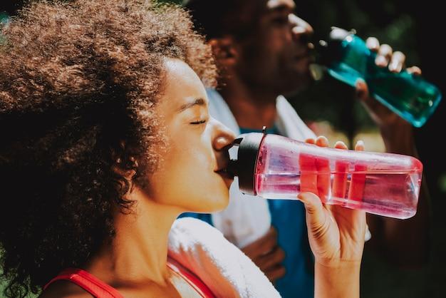 Casal africano americano bebendo água em madeira