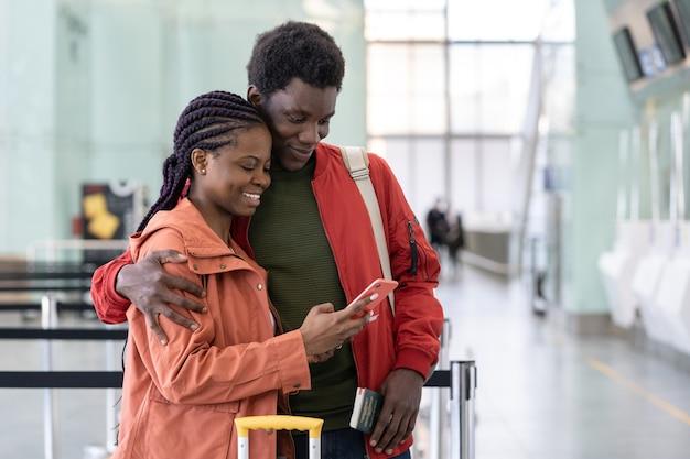 Casal africano animado olhando para o telefone no aeroporto