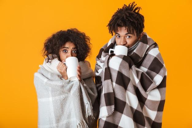 Casal africano congelado enrolado em cobertores aconchegantes bebendo chá quente isolado
