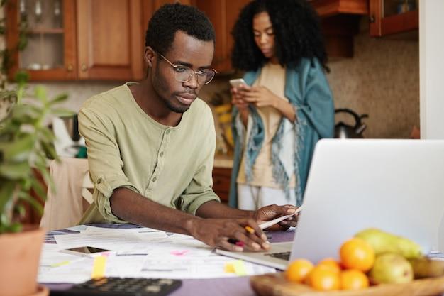Casal africano enfrentando problemas financeiros. homem sério de óculos, calculando as despesas domésticas, usando o computador laptop, sentado à mesa da cozinha com muitos papéis. orçamento familiar e dívidas
