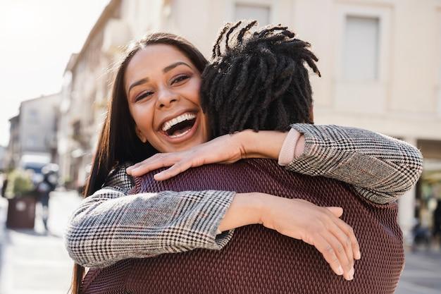 Casal africano feliz se divertindo, abraçando ao ar livre na cidade - concentre-se no rosto da menina