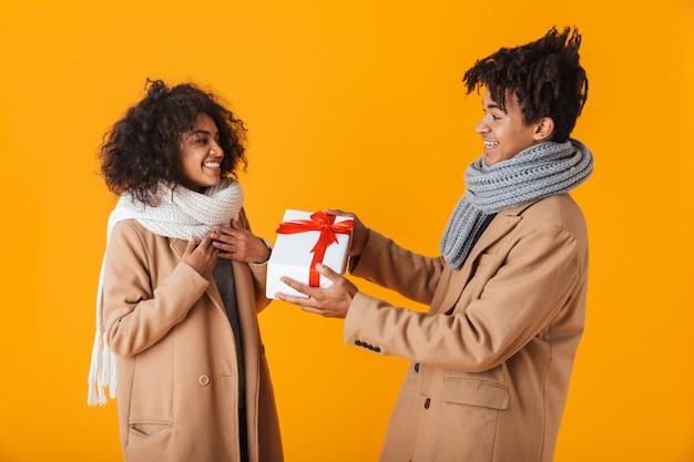 Casal africano feliz vestindo roupas de inverno, isolado, dando presentes