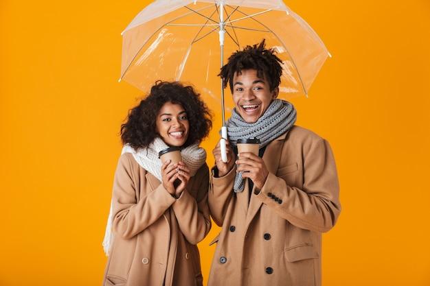Casal africano feliz, vestindo roupas de inverno, parado sob um guarda-chuva isolado, segurando xícaras de café para viagem