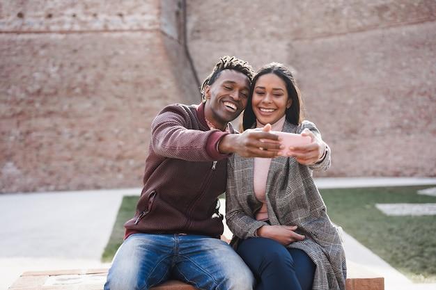 Casal africano se divertindo fazendo selfie ao ar livre na cidade - foco no rosto da mulher