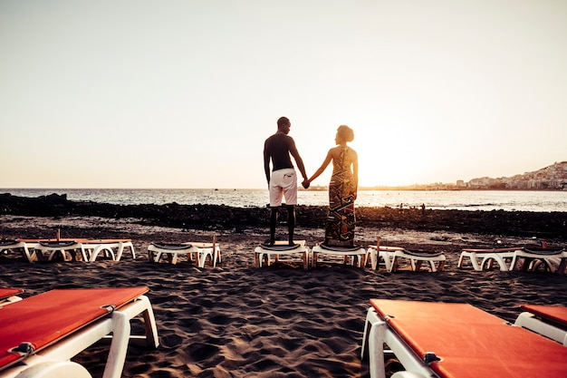 Casal afro-americano de raça negra se divertindo e brincando juntos na caminhada perto da praia. conceito de felicidade de férias para dois lindos rapazes e moças