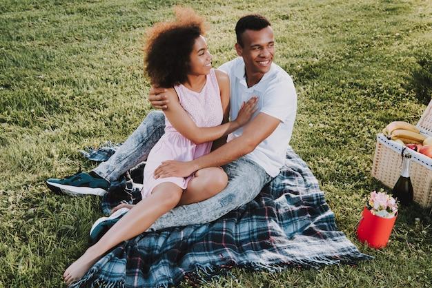 Casal afro-americano está descansando no parque no verão