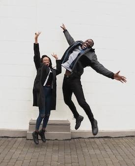 Casal afro-americano feliz pulando tiro completo