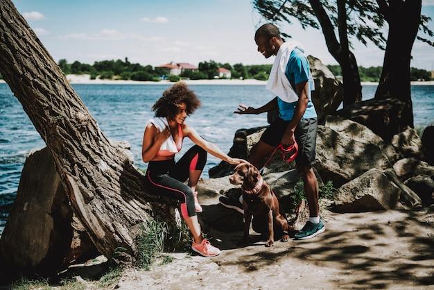 Casal afro-americano na beira do rio com cachorro grande
