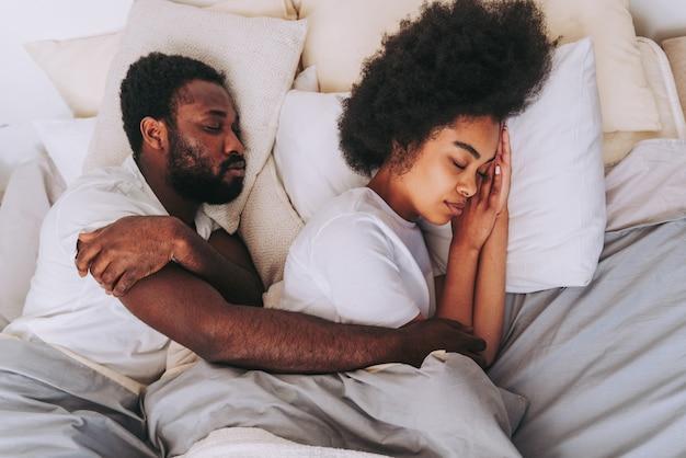 Casal afro-americano na cama - casal de namorados lindos e alegres em casa