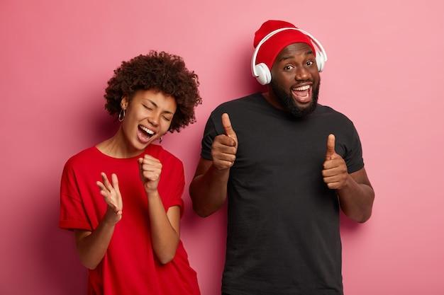 Casal afro-americano tem rostos felizes e relaxados, pega afinação e gosta de música, se diverte na festa, gosta de melodias legais para dançar, mulher canta junto com a música