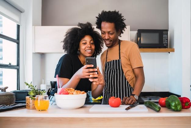 Casal afro cozinhando juntos e usando o telefone em casa.