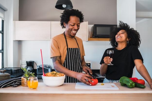 Casal afro cozinhando na cozinha.